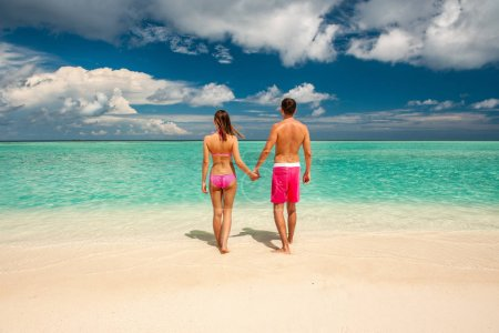 Couple standing on tropical beach at Maldives