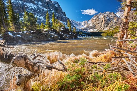 The Loch Lake with rocks and mountains in snow around at autumn. Icicles on trees created by wind and water. Rocky Mountain National Park in Colorado, USA.
