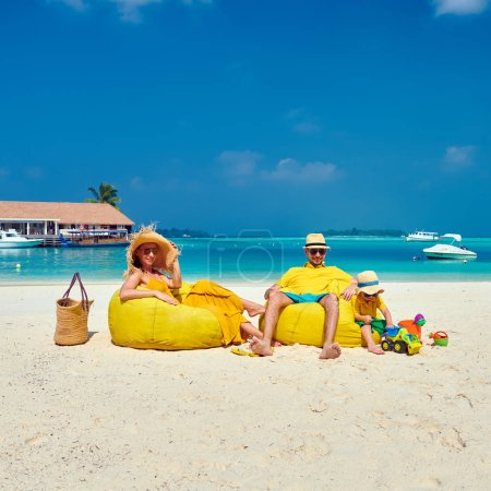 Photo for Family on beach, young couple in yellow with three year old boy. Summer vacation at Maldives. - Royalty Free Image