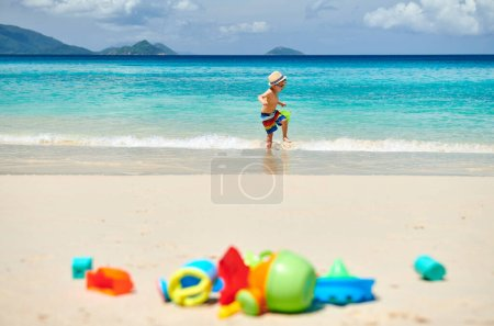 Photo for Three year old toddler boy playing with beach toys on beach. Summer family vacation at Seychelles, Mahe. - Royalty Free Image