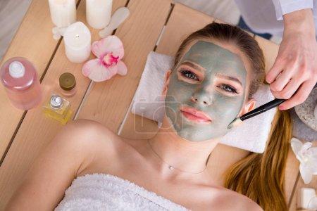 Junge Frau im Wellness-Gesundheitskonzept mit Gesichtsmaske