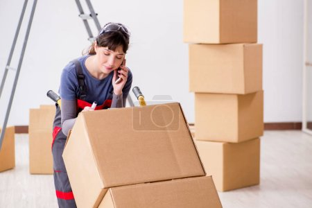 Photo for Woman contractor moving boxes in relocation concept - Royalty Free Image