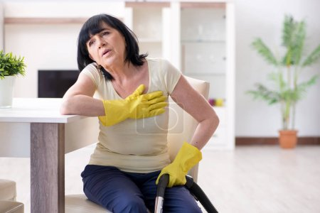 Photo for Senior old woman tired after vacuum cleaning house - Royalty Free Image