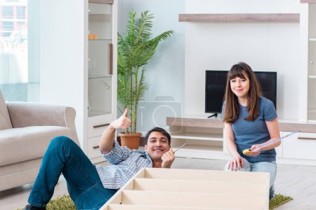 Photo pour Jeune famille assemblant des meubles dans une nouvelle maison - image libre de droit