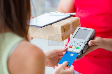 Photo for Parcel delivery being paid with pos and credit card - Royalty Free Image