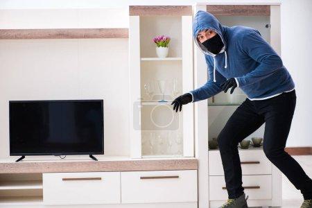 Photo pour Homme cambrioleur voler le téléviseur de la maison - image libre de droit