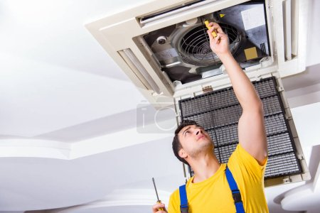 Photo for Repairman repairing ceiling air conditioning unit - Royalty Free Image
