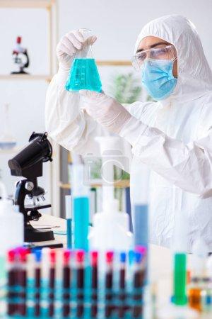 Photo pour Jeune étudiant chimiste travaillant en laboratoire sur les produits chimiques - image libre de droit