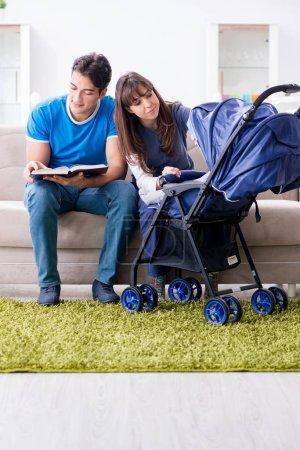 Photo pour Jeunes parents avec leur nouveau-né en landau assis sur le canapé - image libre de droit