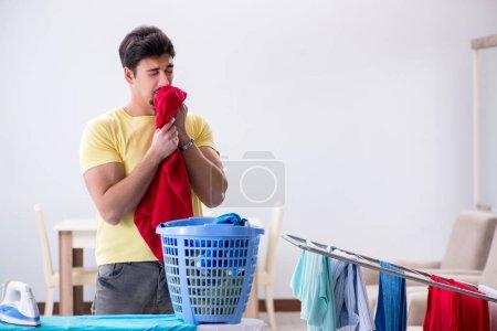 Photo pour Beau mari homme faisant vêtements repassage à la maison - image libre de droit