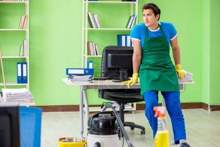 Photo pour Bel homme nettoyage bureau avec aspirateur - image libre de droit