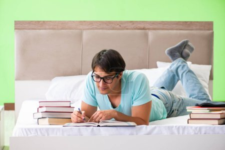 Student preparing for exams at home in bedroom lying on the bed