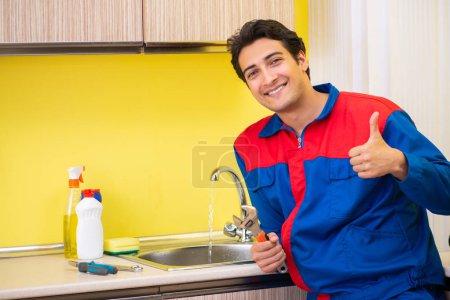 Photo for Plumber repairing tap at kitchen - Royalty Free Image