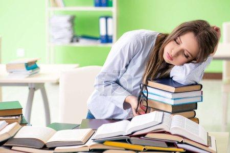 Photo pour Jeune étudiante se préparant à des examens avec de nombreux livres - image libre de droit