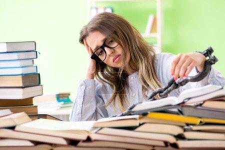 Photo pour Jeune étudiante enchaînée au bureau et se préparant aux examens avec de nombreux livres - image libre de droit