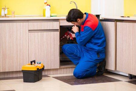 Photo pour Plombier réparer lavabo à la cuisine - image libre de droit