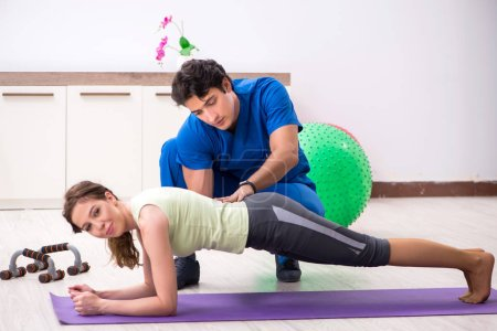 Photo for Fitness instructor helping sportsman during exercise - Royalty Free Image