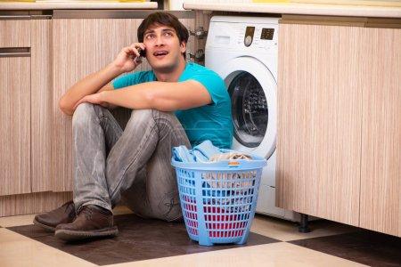 Photo pour Homme jeune époux faisant la lessive à la maison - image libre de droit