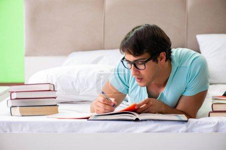 Photo pour Étudiant se préparant pour les examens à la maison dans la chambre couchée sur le lit - image libre de droit