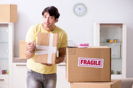 Photo for Man moving house and relocating with fragile items - Royalty Free Image