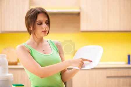 Photo pour Jeune femme nettoyage et lavage de la vaisselle dans la cuisine - image libre de droit
