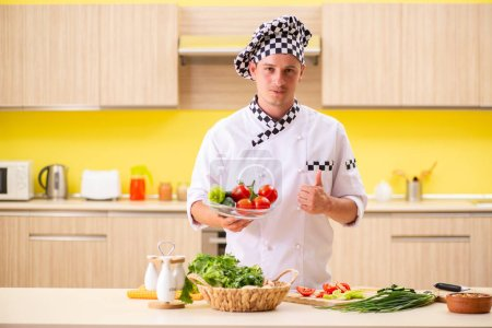 Photo for Young professional cook preparing salad at kitchen - Royalty Free Image