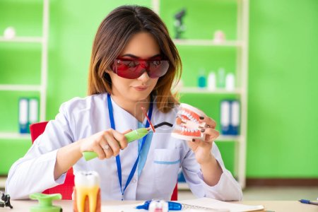 Photo pour Femme dentiste travaillant sur implant dentaire - image libre de droit