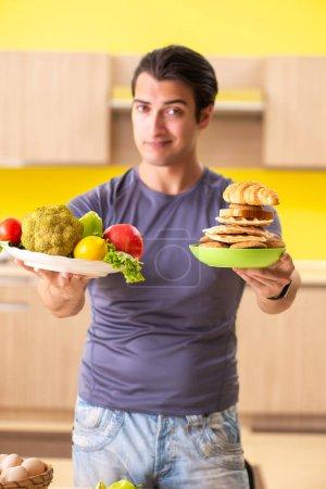 Photo for Man having hard choice between healthy and unhealthy food - Royalty Free Image