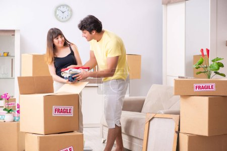 Photo for Young couple moving to new flat with fragile things - Royalty Free Image