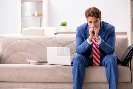 Photo pour Jeune homme d'affaires travaillant à la maison assis sur le canapé - image libre de droit