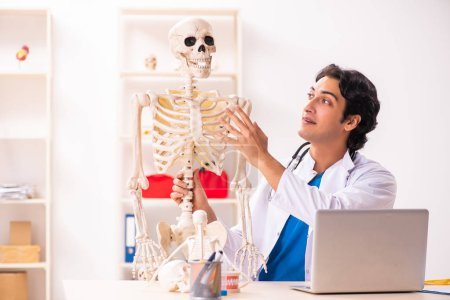 Photo for Young male doctor with skeleton - Royalty Free Image