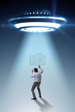 Photo for Flying saucer abducting young businessman - Royalty Free Image