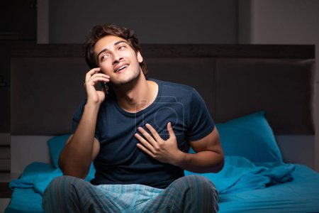 Photo for Young man talking on mobile late at night - Royalty Free Image
