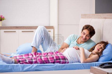 Kobieta w ciąży z mężem w sypialni