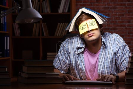 Photo for Young handsome student preparing for exams at night - Royalty Free Image