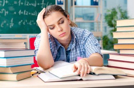 Photo pour Étudiante avec de nombreux livres assis dans la salle de classe - image libre de droit