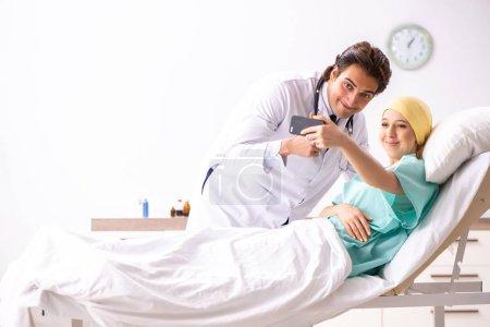 Photo pour Jeune beau docteur visite patient oncologie femelle - image libre de droit