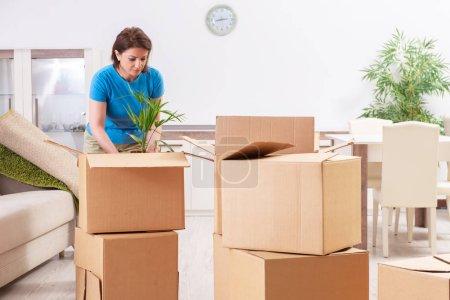 Frau mittleren Alters zieht in neue Wohnung