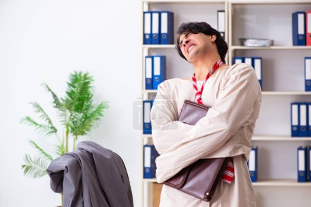 Photo for Crazy young man in straitjacket at the office - Royalty Free Image