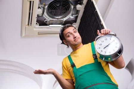 Photo pour Jeune réparateur réparant unité de climatisation de plafond - image libre de droit