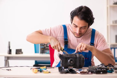 Photo for Young male contractor repairing computer - Royalty Free Image