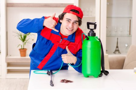 Young contractor doing pest control at home
