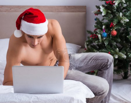Photo for The sexy man in the bed wearing santa hat in christmas concept - Royalty Free Image