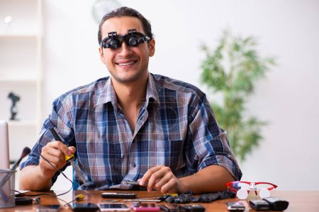Photo for Young male technician repairing the mobile phone - Royalty Free Image