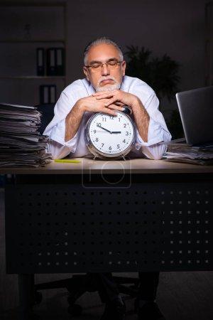 Photo pour Ancien employé masculin travaillant tard sur le lieu de travail - image libre de droit