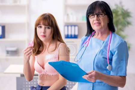 Mujer joven que visita al viejo oncólogo médico en cáncer de mama