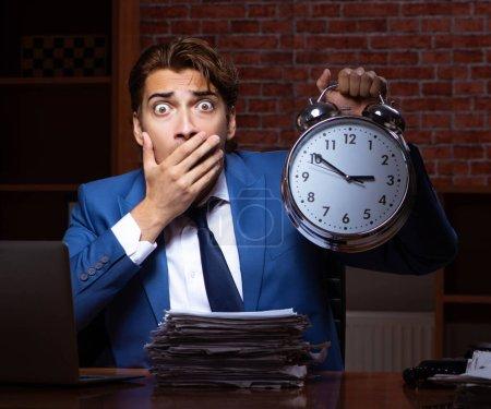 Photo pour Le jeune homme d'affaires travaillant dans le bureau la nuit - image libre de droit