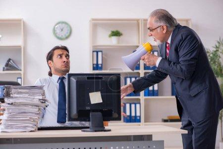Photo pour Ancien patron et jeune employé dans le bureau - image libre de droit