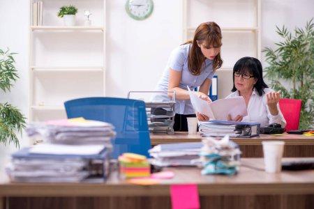 Photo pour Deux employés et un travail excessif au bureau - image libre de droit