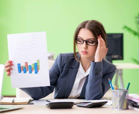 Photo pour Directrice financière présentant un graphique assis dans le bureau - image libre de droit
